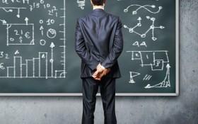 mansperson står framför svarta tavlan med matematiska symboler