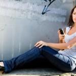 tjej som skickar sms på sin mobiltelefon