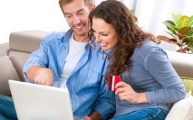 par som sitter i soffan med laptop